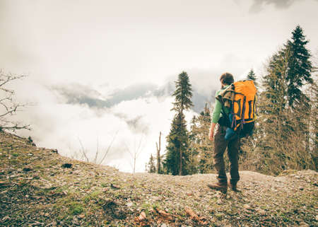 Young Man with backpack relaxing outdoor with foggy mountains on background Lifestyle Travel concept Summer vacations Imagens