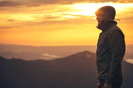 Giovane uomo in piedi da solo all'aperto con montagne Tramonto su Lifestyle sfondo concetto di viaggio e di sopravvivenza