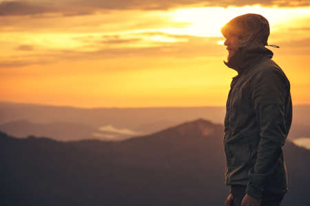 Young Man standing alone outdoor with sunset mountains on background Travel Lifestyle and survival concept Imagens
