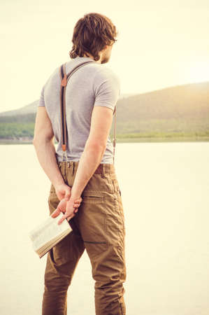 intelligent: Young Man standing with book outdoor with scandinavian lake on background Education and Lifestyle Travel concept