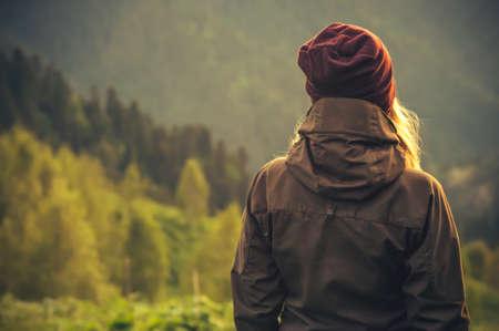 生活方式: 年輕女子在背景的旅遊生活方式和生存理念後視獨自站在戶外與野生森林山 版權商用圖片