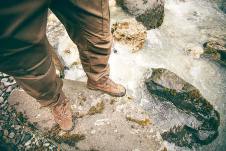 river view: Feet Man trekking boots hiking outdoor Lifestyle Travel survival concept with river and stones on background top view