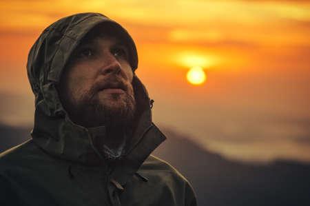 Человек Путешественник бородатое лицо в покое на открытом воздухе с захода солнца горы на фоне Путешествие выживания Образ жизни и эмоции концепции
