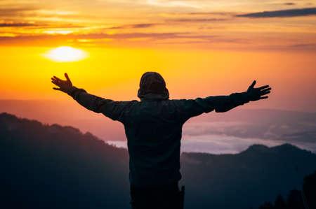 manos levantadas al cielo: El hombre manos de viajero criados al aire libre con la silueta de montañas cielo puesta de sol sobre el estilo de vida Antecedentes de viajes y emociones concepto de la felicidad Foto de archivo