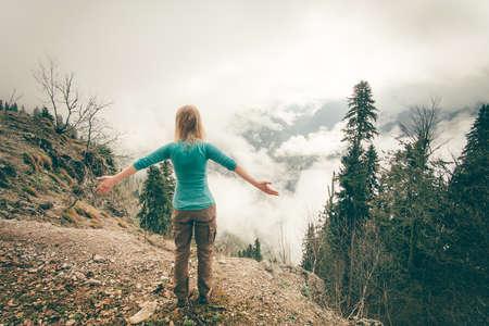 Молодая женщина подняла руки расслабляющий на открытом воздухе с туманного леса на фоне Стиль жизни Концепция Путешествия Летние каникулы вид сзади Фото со стока