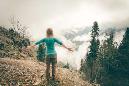 Young Woman raised hands relaxing outdoor with foggy forest on background Lifestyle Travel concept Summer vacations rear view
