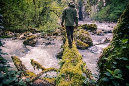 Hombre de viajeros de cruce del río en registro al aire libre estilo de vida del concepto del recorrido de supervivencia Foto de archivo