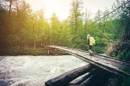 Žena cestovatel s batohem turistiku na mostě přes řeku jezdit životní styl koncept lesa na pozadí letní cestovní prázdnin Venkovní