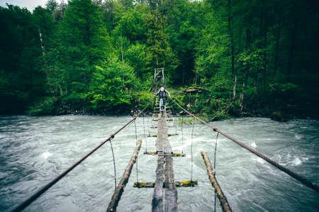 Hombre de viajeros de senderismo en el puente de madera sobre el río Destinos vacaciones en el estilo de vida concepto de viaje verano al aire libre Foto de archivo