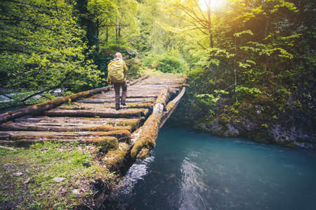 Woman Traveler with backpack hiking on bridge over river Travel Lifestyle concept forest on background Summer journey vacations outdoor Imagens