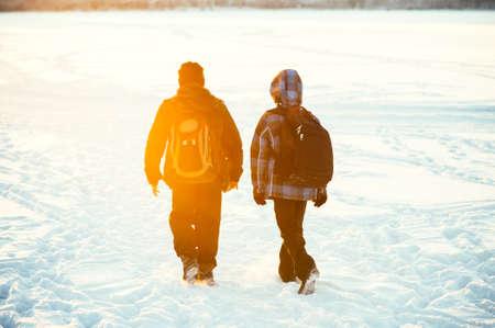De vrienden van kinderen lopen met de school rugzakken Winter besneeuwde weer