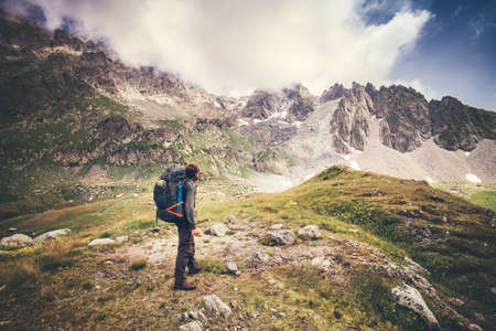 Man Traveler with big backpack mountaineering Travel Lifestyle concept rocky mountains and clouds on background Summer adventure vacations outdoor