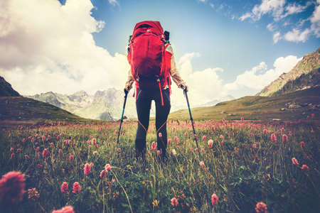 Woman Traveler with red backpack hiking Travel Lifestyle concept Summer vacations outdoor mountains and flowers valley on background