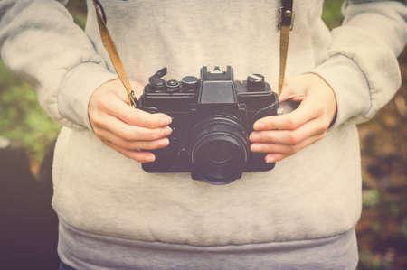 voyage: Femme mains tenant appareil photo rétro marche Lifestyle hippie concept Voyage en plein air rétro couleurs