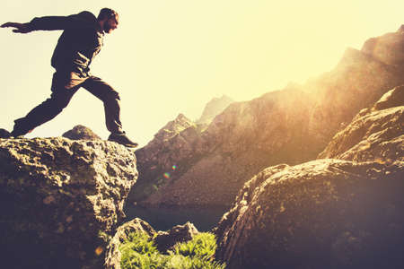 outdoor sport: Man running on Mountains jumping cliff over lake Skyrunning sport Lifestyle Travel concept outdoor