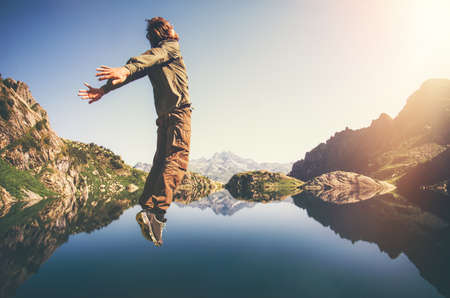 levitation: Happy Man Flying levitation jumping with lake and mountains on background Lifestyle Travel emotions concept outdoor