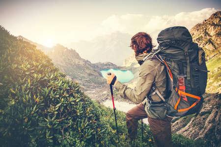 Man Reisenden mit großem Rucksack Bergsteigen Travel Lifestyle-Konzept See und die Berge im Hintergrund Sommer extreme Urlaub outdoor