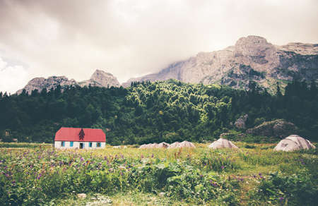 cloudy moody: Rocky Mountains Camping Valley with touristic tents and house Landscape cloudy moody sky Summer Travel scenic view Stock Photo