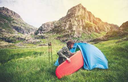 Man Traveler with camping equipment mattress and tent outdoor Travel Lifestyle concept rocky mountains landscape on background Summer journey adventure vacations Standard-Bild
