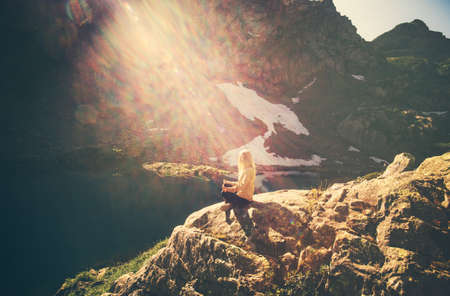mujeres orando: Woman meditating yoga sitting on cliff alone sun light Travel healthy Lifestyle concept lake and rocky mountains landscape on background outdoor Foto de archivo