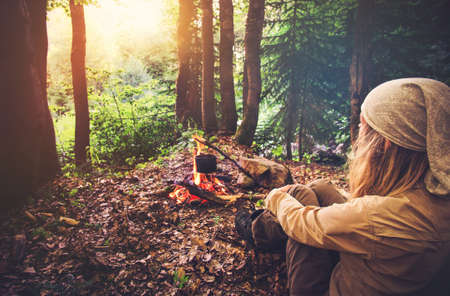 girl in the forest: Woman traveler relaxing in forest and cooking food in kettle on fire Travel Lifestyle concept vacations outdoor picnic bivouac in forest Stock Photo