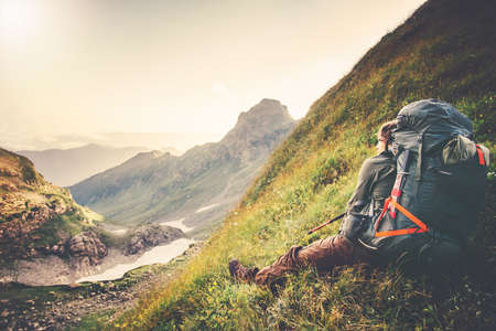 expedition: Man Traveler with big backpack relaxing alone Travel Lifestyle concept sunset mountains landscape on background Summer adventure expedition outdoor