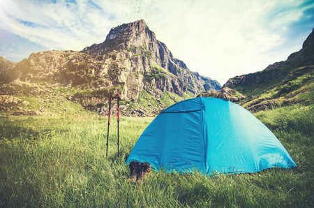 boot camp: Rocky Mountains Landscape and tent camping with trekking poles and boots Travel Lifestyle concept Summer adventure vacations outdoor