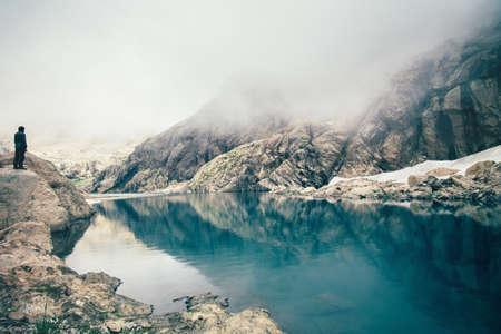 クリフ湖と背景の旅行ライフ スタイルの感動的なコンセプトの屋外を霧山に単独で立っている男性旅行者 写真素材