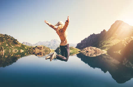 levitation: Happy Woman jumping up Flying levitation with lake and mountains on background Lifestyle Travel emotions concept outdoor