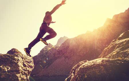 Corredor do homem em montanhas pulando do penhasco sobre o lago Skyrunning esporte Estilo de vida conceito de viagem ao ar livre