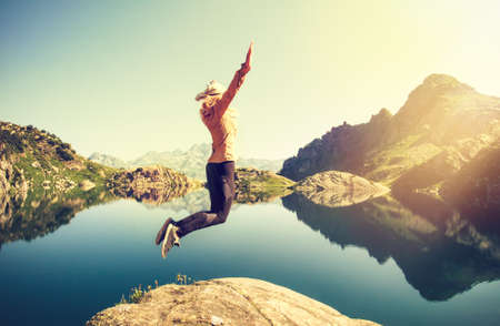 levitation: Woman hiker jumping up Flying levitation with lake and mountains on background Lifestyle Travel emotions concept outdoor Stock Photo