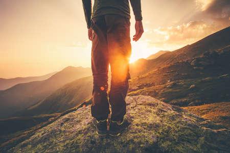 Jóvenes pies del hombre viajero de pie por sí solo con las montañas del sol en el fondo del concepto del recorrido al aire libre de estilo de vida
