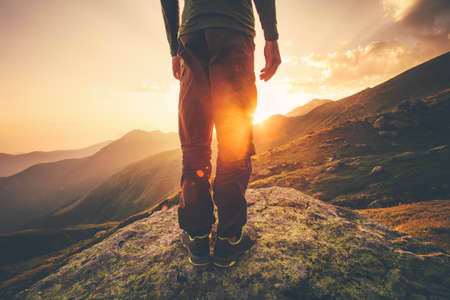 Young Man Traveler feet standing alone with sunset mountains on background Lifestyle Travel concept outdoor