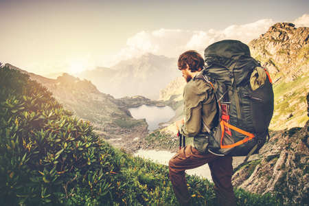 Man Traveler with big backpack mountaineering Travel Lifestyle concept lake and mountains on background Summer adventure vacations outdoor
