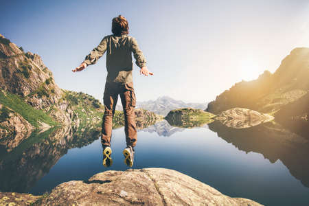 man flying: Man jumping Flying levitation with lake and mountains on background Lifestyle Travel happy emotions concept outdoor Stock Photo