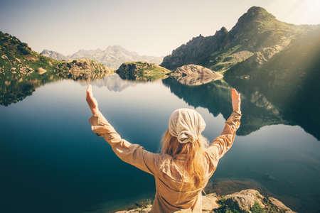 Mujer meditando viajeros armonía con la naturaleza del viaje estilo de vida saludable concepto lago y las montañas rocosas en el fondo del paisaje al aire libre Foto de archivo