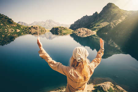 salud y deporte: Mujer meditando viajeros armonía con la naturaleza del viaje estilo de vida saludable concepto lago y las montañas rocosas en el fondo del paisaje al aire libre