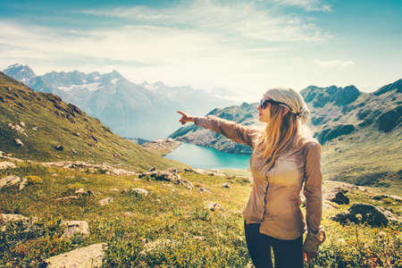 Traveler Woman hand showing destination Travel Lifestyle concept serene view lake and mountains landscape on background summer vacations outdoor