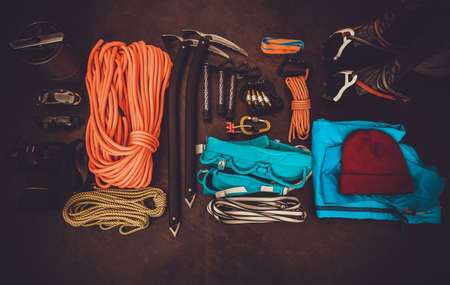 Climbing equipment set: orange rope, crampons, ice axe, shoes, harness and other set on dark background Travel lifestyle trendy concept top view