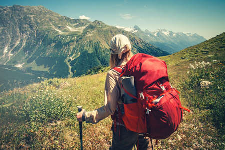 Traveler with red backpack hiking Travel Lifestyle concept active adventure vacations outdoor mountains on background