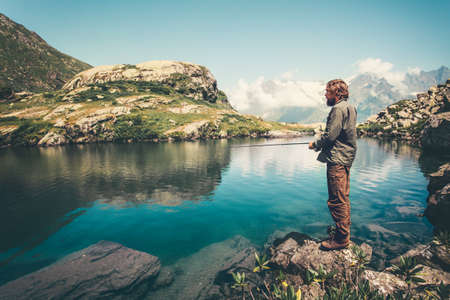 Man Fisherman fishing with rod lake and mountains on background Lifestyle Travel hobby concept active summer vacations