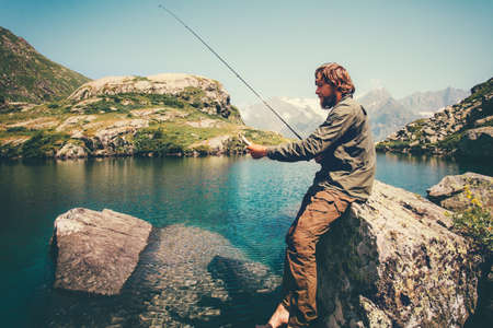 Young Man fishing on Lake with rod mountains on background Travel Lifestyle concept summer vacations