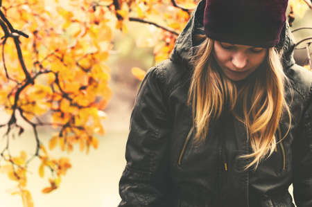 melancholy: Sad Woman walking in park with autumn leaves on background outdoor Seasonal melancholy Lifestyle concept Stock Photo