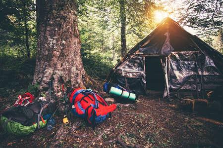 林の背景に自然のバックパックと廃屋キャンプ旅行アウトドア ハイキングの装備 写真素材