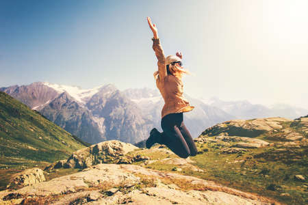 Happy Woman jumping up Flying levitation with mountains landscape on background Lifestyle Travel emotions success concept outdoor Archivio Fotografico