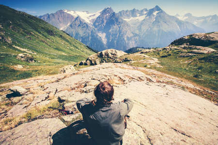 Traveler Man relaxing Travel Lifestyle concept beautiful mountains landscape on background adventure vacations outdoor rear view
