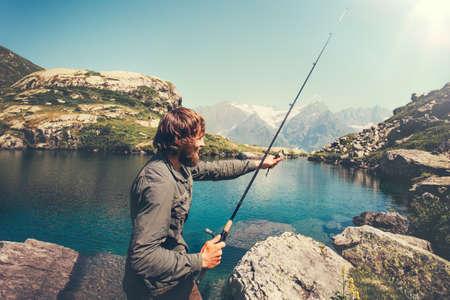 Man Fischer Fischen mit Rod allein See und Berge Landschaft im Hintergrund Lifestyle Travel Überleben Konzept Lizenzfreie Bilder - 69743598