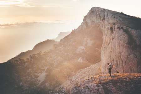 epic: Woman Traveler with backpack hiking on cliff Travel Lifestyle concept adventure active vacations outdoor rocky mountains sunset Landscape