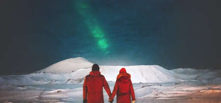epic: Couple Travelers enjoying Northern lights view above mountains holding hands Travel Lifestyle and love relationship feelings concept vacations into the wild night scene