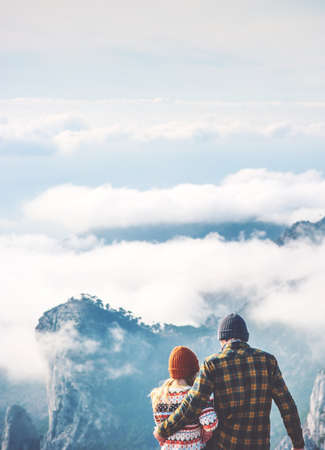 Couple lovers Man and Woman hugging enjoying mountains and clouds landscape on background Love and Travel happy emotions Lifestyle concept. Young family traveling active adventure vacations